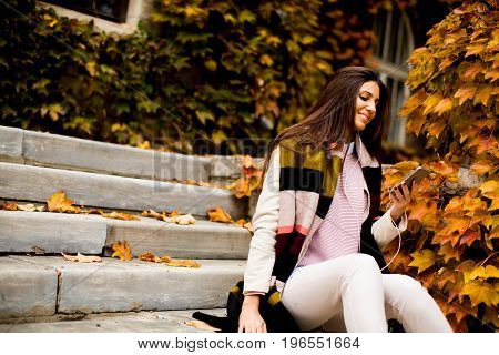 Pretty Young Woman With Mobile Phone In Autumn Park
