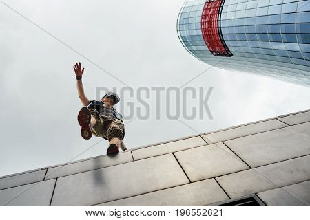Stylish man experiencing virtual reality using oculus goggles with head-mounted display standing on edge of skyscraper about to fall down. Gaming 3d technology cyberspace and entertainment