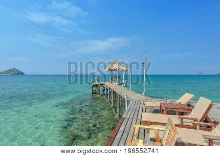 Wooden chair on pier in sea with beautiful tropical island Thailand