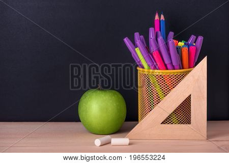 Education Concept With Green Apple, Ruler Or Triangle, Felt Pens, Chalks Over Black Chalkboard Backg