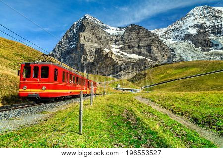 Famous electric retro red tourist train coming down from the Jungfraujoch station(top of Europe) in Kleine Scheidegg Bernese Oberland Switzerland Europe