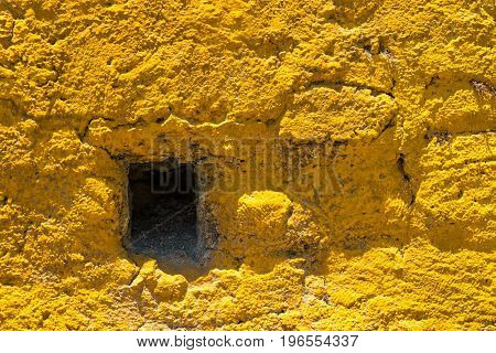 old stone wall of yellow color with a square hole