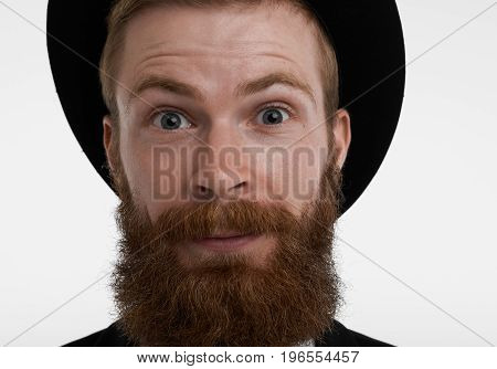 Close up highly-detailed portrait of astonished redhead bearded man in elegant hat raising eyebrows in surprise amused with positive unexpected news. Human emotions feelings reaction and attitude