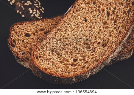 Rye bread slices at black background. Fresh black bread with cumin and sesame