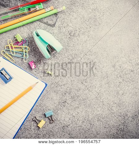 Assorted colorful school supplies on gray stone background. Concept with copy space. Retro style toned.