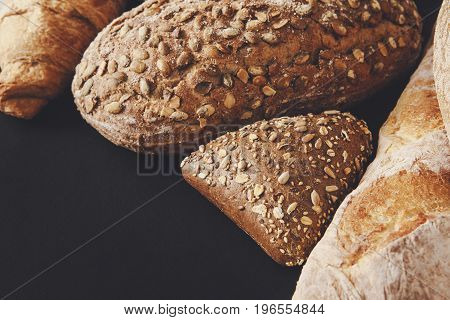 Bakery background, bread assortment on black with copy space. Rye buns, french baguette and croissant, isolated