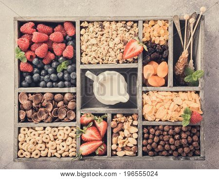 Variety of cold quick breakfast cereals with berries in old gray wooden box and other ingredients for breakfast, healthy eating concept, top view. Retro style toned.