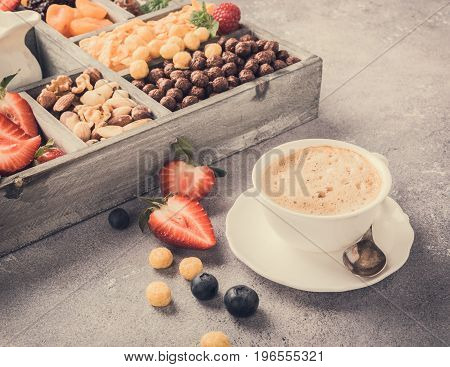 Healthy breakfast with coffee, variety of cold quick breakfast cereals and berries in old gray wooden box, selective focus. Retro style toned.