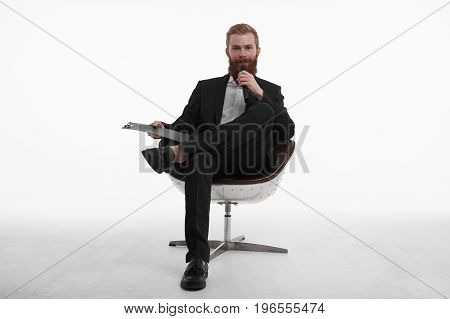 Live broadcasting. Portrait of confident young male professional news reporter with red beard sitting in chair in relaxed pose holding clipboard and talking in microphone dressed in stylish suit