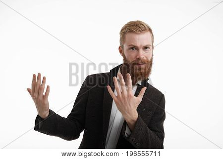 Adverising concept. Business career and occupation. Good-looking red-haired young businessman wearing elegant suit posing against white studio wall background and holding hands showing something