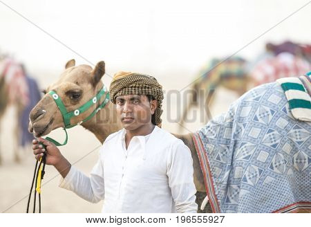Rub al Khali Desert Abu Dhabi United Arab Emirates July 22nd 2017: man with his camel at a camel track in a desert