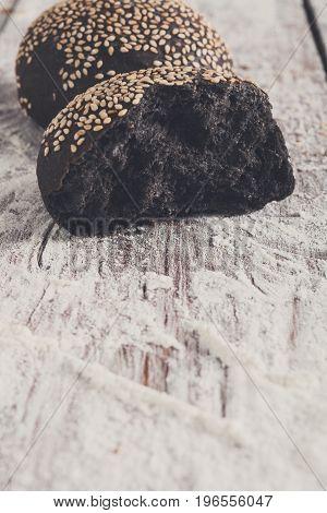 Fresh black carbon bun crust half. Bread on rustic wood, copy space