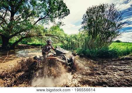 VITEBSK, BELARUS - JUNE 11, 2017: Photo of man on the ATV Quad Bike running in mud track.