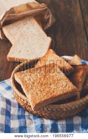 Breakfast background, white bread toasts in wicker breadbasket on checkered table napkin half covering wooden table, closeup, vertical
