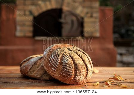 Rustic handmade bread on a wooden table against the background of the furnace