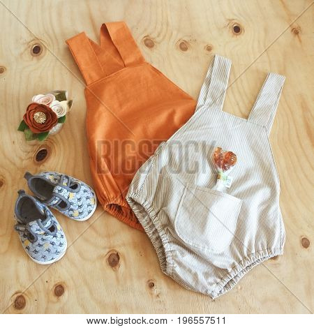 Children's clothing on a wooden background square photo