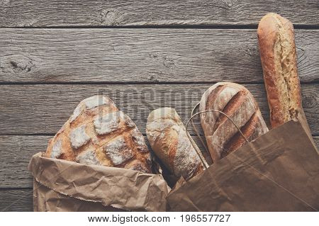 Bread border on rustic wood with copy space background. Brown and white loaves in paper bags
