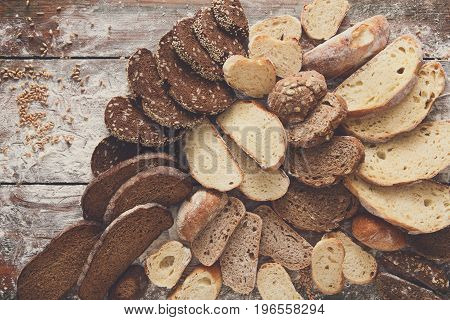 Sliced bread background on rustic wood, copy space. Brown and white loaves and flour top view composition with wheat flour sprinkled around.