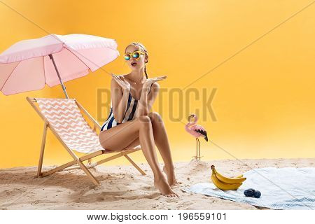 Beautiful girl in swimsuit with colourful sunglasses looks surprised on bright background of summer decor