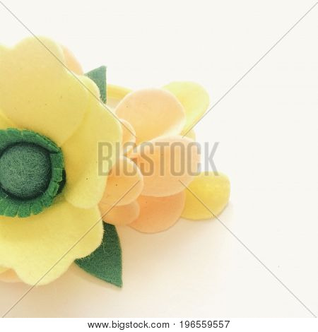 Yellow handmade flower on a light background. Square photo