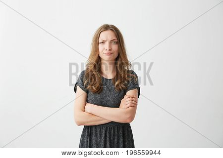 Portrait of displeased young pretty girl looking at camera with contempt over white background. Crossed arms. Copy space.