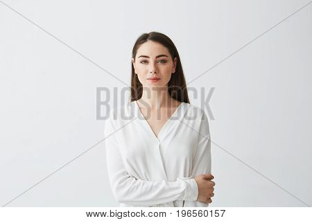 Portrait of young beautiful businesswoman looking at camera smiling over white background. Copy space.