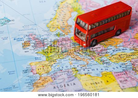 Travelling abroad by bus concept. Red doubbledecker on the map, group tour to europe. Tourism and vacation background, closeup