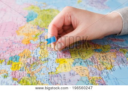 Travelling background. Female hand tackling country with flag-pin on the map. Tourism and vacation concept