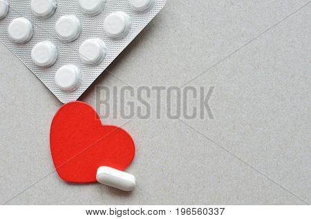 red heart with packing full of pills over gray background, healthy life concept, copy space