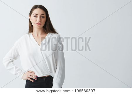 Portrait of young beautiful brunette businesswoman smiling looking at camera posing over white background. Copy space.