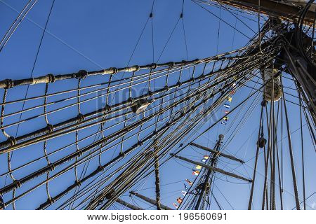 Nautical part of a yacht or a big old sailing ship with cords, rigging, sail, masts, knots, signal flags in front of a blue sky