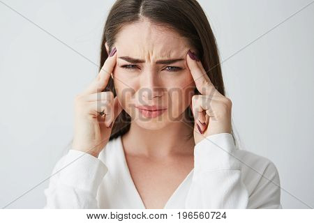 Young beautiful brunette businesswoman holding fingers on temples frowning from pain over white background. Headache. Copy space.