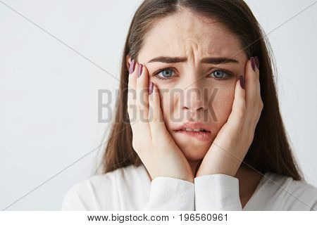 Close up photo of displeased frightened girl looking at camera touching face frowning over white background. Copy space.