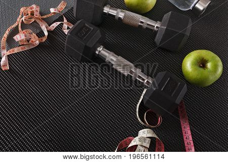 Fitness equipment. Healthy lifestyle. Dumbbells, water, apple and measuring tape on black background, copy space
