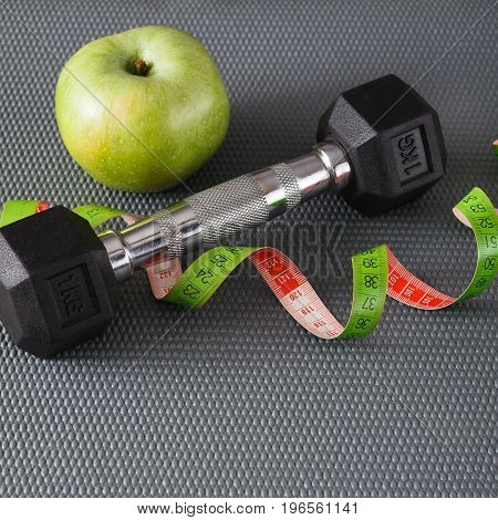 Fitness equipment. Healthy lifestyle. Dumbbells, apple and measuring tape on gray background