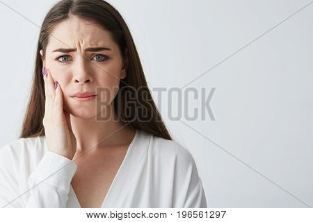 Sad upset young girl looking at camera with hand on face over white background. Copy space.