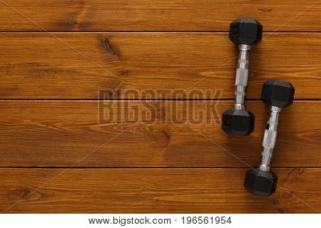 Two dumbbells on wooden background copy space. Weight exercise, powerlifting, bodybuilding concept