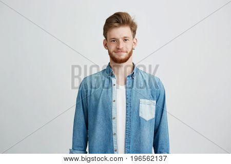 Portrait of young handsome man in jean shirt smiling looking at camera over white background. Copy space.
