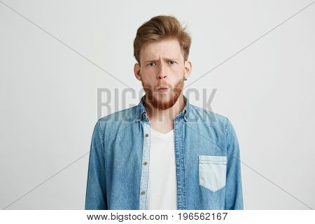 Portrait of young emotive shocked man frowning looking at camera over white background. Copy space.