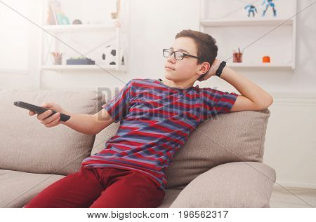 Teenager boy watching television, using TV remote while sitting on couch in living room at home