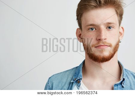 Portrait of young handsome man with beard looking at camera over white background. Copy space.