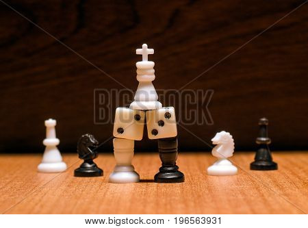 Chess king on dice on a light wooden surface on a background of dark wood around chess pieces horses and officers