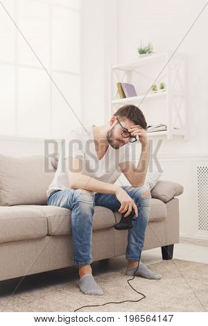 Sda young man playing video games at home and loses. Guy sitting on the couch with joystick in hands, copy space