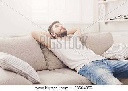 Time to relax. Handsome young man in casual holding hands behind head while dreaming on the couch