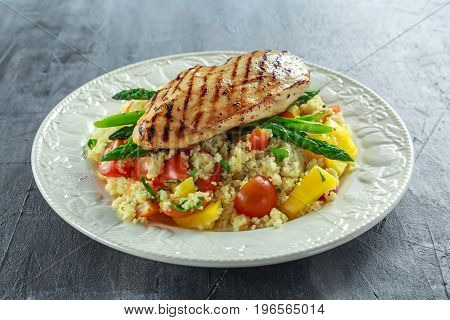 couscous salad with grilled chicken and asparagus on white plate. healthy food.