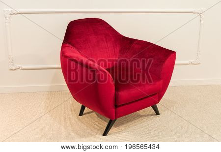 Red armchair on legs against white wall background