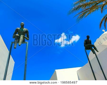 Oia, Santorini, Greece - June 10, 2015: Sculpture of sitting men as decoration of old building in Oia town, Santorini island Oia is a very popular city among tourists on Santorini island