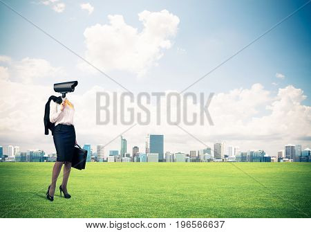 Elegant businesswoman outdoors with suitcase in hand and camera instead of head