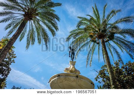 Neptune Under The Palm Tree In Alcazar Garden With A Blue Sky In Seville,  Spain, Europe