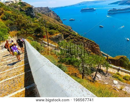 Santorini, Greece - June 10, 2015: The people going at road to the sea from the steps and traditional transport in the form of a donkey at Santorini, Greece on June 10, 2015